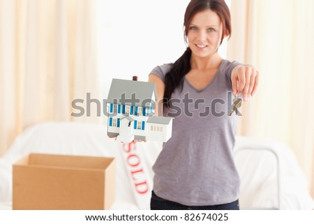 Beautiful woman holding model house and keys in a living room
