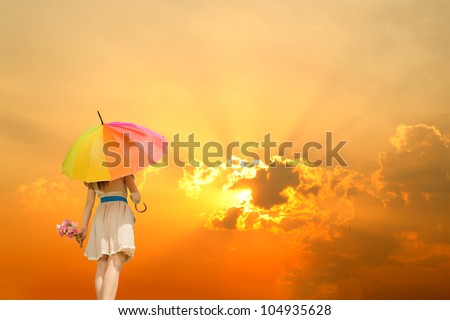 Beautiful woman holding multicolored umbrella and sunset
