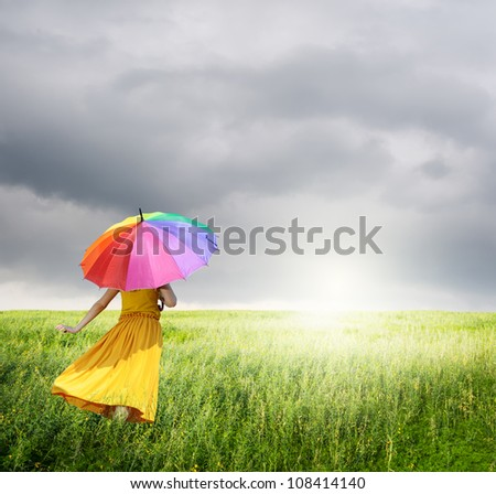 Beautiful woman holding multicolored umbrella in green grass field and raincloud
