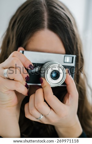 beautiful woman holding old camera at home