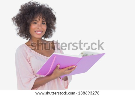 Beautiful woman holding photo album and smiling at camera on white background