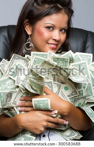 Beautiful woman holding pile of money - stock photo