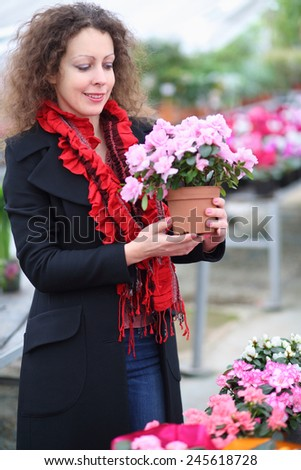 Beautiful woman holding pot with beauty flower in the greenhouse - stock photo