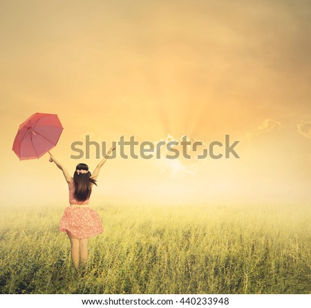 Beautiful woman holding red umbrella in grass field and sunset.Vintage tone. - stock photo
