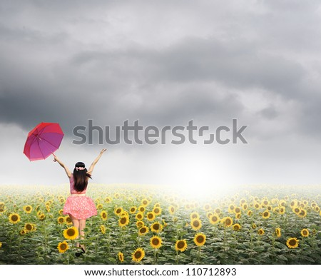 Beautiful woman holding red umbrella in sunflower field and rainclouds