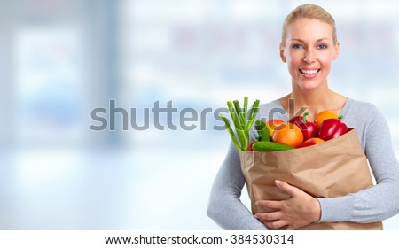 Beautiful woman holding shopping bag with food. - stock photo