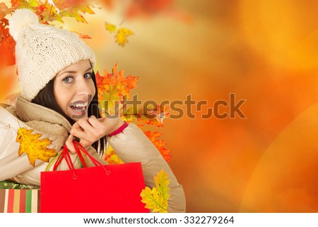 Beautiful woman holding shopping bags, buying in autumn season. - stock photo