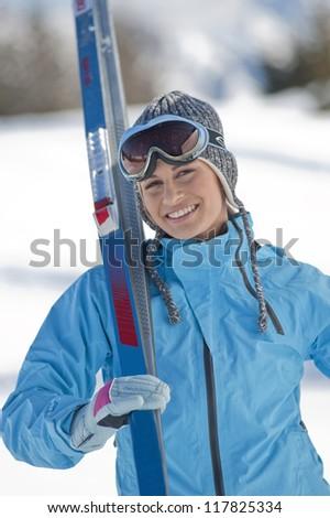 Beautiful woman holding skis - stock photo