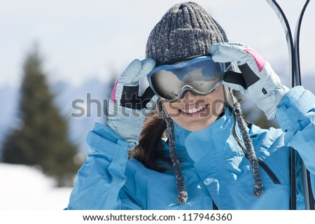 Beautiful woman holding skis and looking at camera