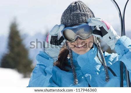 Beautiful woman holding skis and looking at camera - stock photo