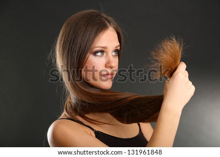Beautiful woman holding split ends of her long hair,  on black background - stock photo