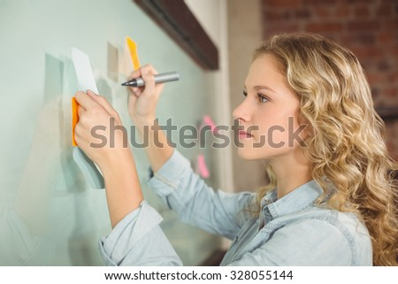 Beautiful woman holding sticky note while writing on glass board in creative office - stock photo