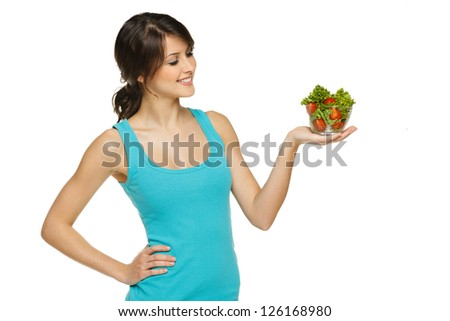 Beautiful woman holding transparent bowl with healthy salad meal, looking at bowl, over white, with copy space