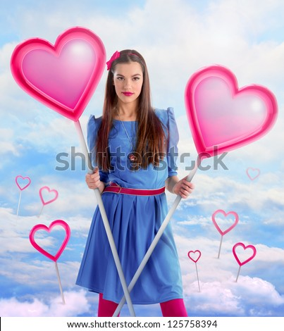 Beautiful woman holding  two hearts over a sky background - stock photo