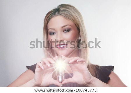 beautiful woman holding up a light bulbs in her hand with the bulb alight