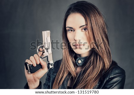 beautiful woman holding up her gun - stock photo