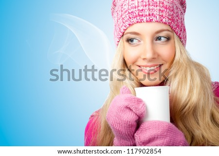 beautiful woman holding white cup of drink over blue - stock photo