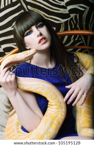 Beautiful woman holding yellow Python - stock photo