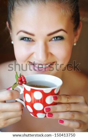 Beautiful woman holds the cup of cowberry tea - stock photo