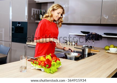 Beautiful woman housewife prepares healthy food in the kitchen. Healthy eating. Home interior. - stock photo