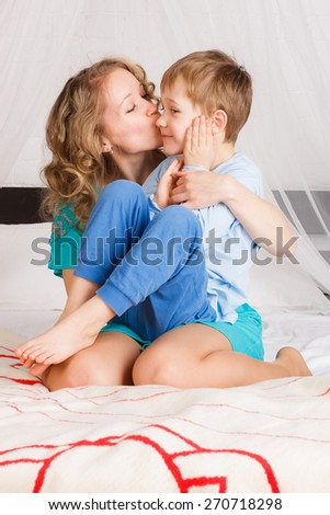 Beautiful woman hugging and kissing her child