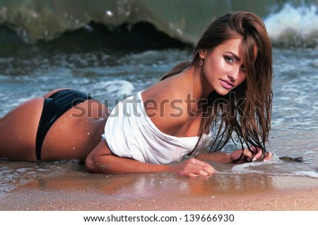 beautiful woman in a bathing suit standing on the beach at sunset - stock photo