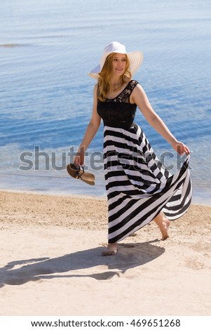 Beautiful woman in a black and white sun-dress walking along the beach.
