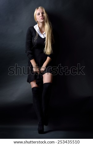 Beautiful woman in a black dress and stockings posing in studio with dark background . - stock photo