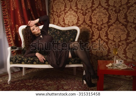 Beautiful woman in a black dress sitting on the couch in the vintage interior - stock photo