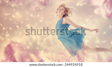 Beautiful woman in a blue dress flying in a pink peony flower fantasy  - stock photo