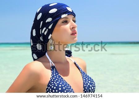beautiful woman in a blue scarf on the beach. blue bikini. arabic style - stock photo