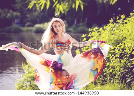 Beautiful woman in a bright dress flying in the forest - stock photo