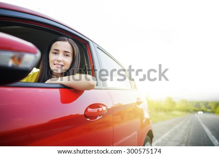 Beautiful woman in a car against the backdrop of receding into the distance the road. - stock photo