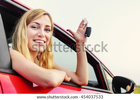 Beautiful woman in a car showing keys.