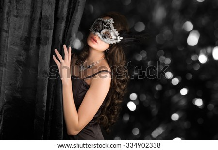 Beautiful woman  in a carnival mask behind the velvet curtain on sparkling dark background. - stock photo
