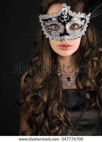 Beautiful woman  in a carnival mask on dark background.  - stock photo
