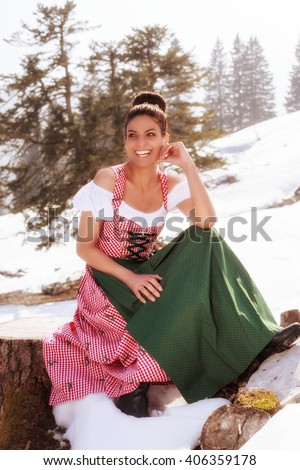 Beautiful woman in a dirndl, sitting in nature on a tree stump in the middle of the snow, smiling at the camera - stock photo