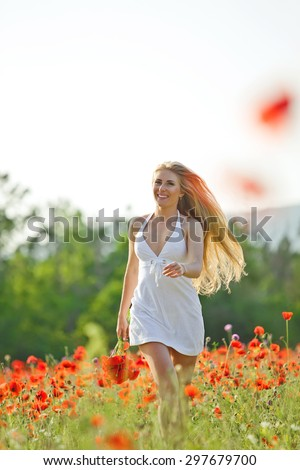 Beautiful woman in a field with flowers - stock photo