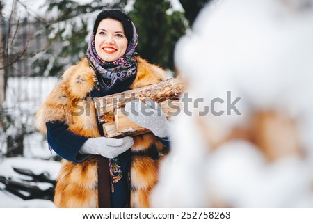 beautiful woman in a fur coat and scarf with firewood. Russian village. Winter.