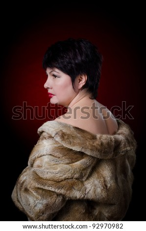 Beautiful woman in a fur coat with naked shoulders - stock photo