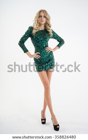 Beautiful woman in a green dress on a white background, with long legs - stock photo