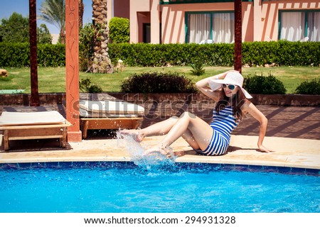 beautiful woman in a hat sitting on the edge of the pool - stock photo