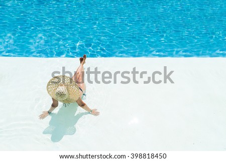 beautiful woman in a hat sitting on the edge of the swimming pool