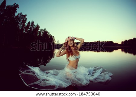 Beautiful woman in a lake at night. Beauty girl at sunset in the lake.