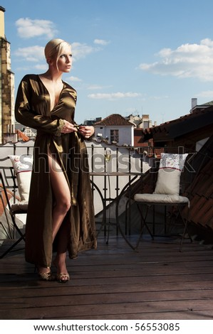 beautiful woman in a negligee posing on the roof terrace - stock photo