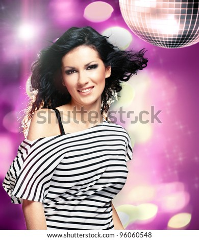 Beautiful woman in a nightclub with big disco ball - stock photo