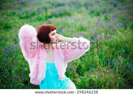 Beautiful woman in a pink fur coat sitting among a field of wild flowers - stock photo