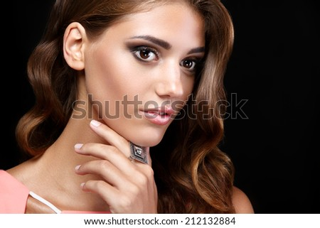 Beautiful woman in a pink romantic dress with smooth wavy hair and smoky eyes make up and a ring on her finger on black background - stock photo