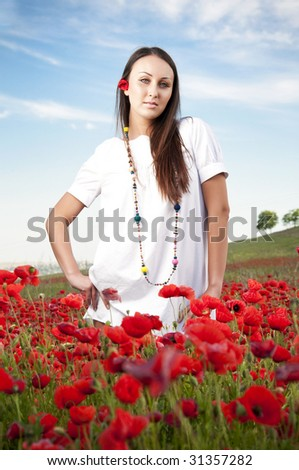 Beautiful woman in a poppy field - stock photo