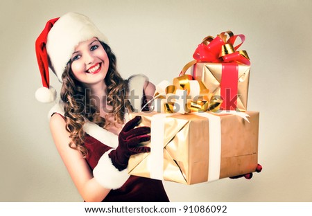 Beautiful woman in a red dress and hat of Santa with a big gift box.